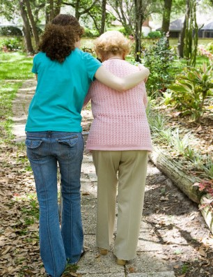Caregiver helping an elderly woman walk down a sidewalk