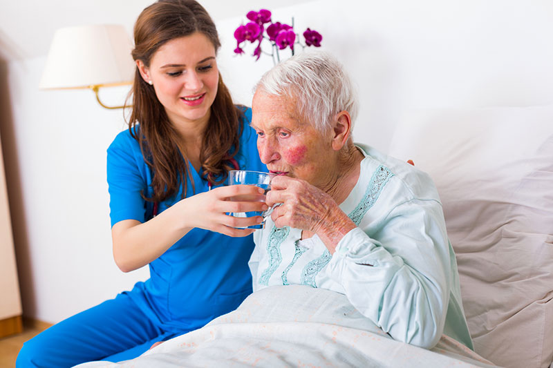 Kind geriatric doctor bringing water to the senior woman in need.