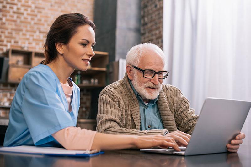 Nurse sitting by senior man using laptop