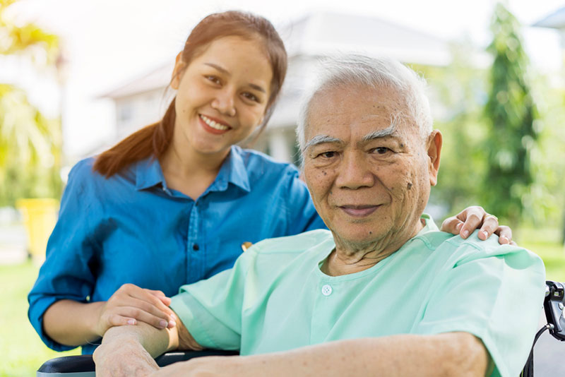 Portrait of Young Asian caregiver in uniform hugging smiling elderly man
