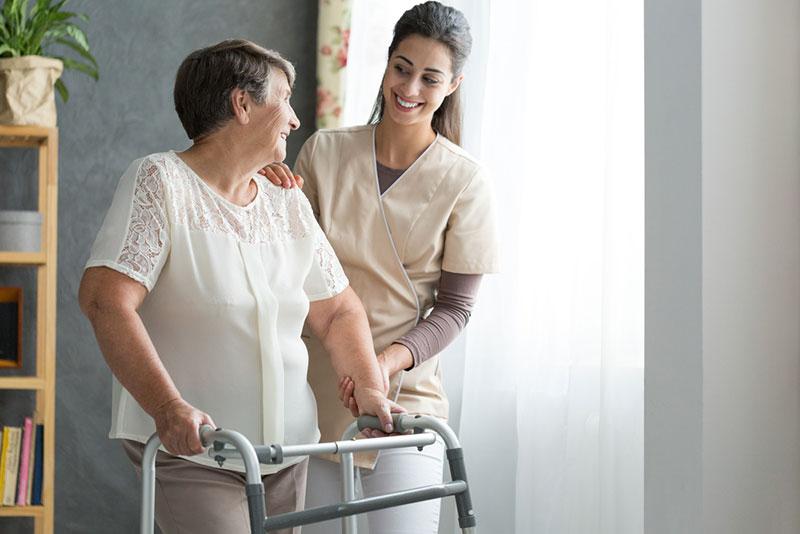 Smiling nurse helping senior lady to walk around the nursing home
