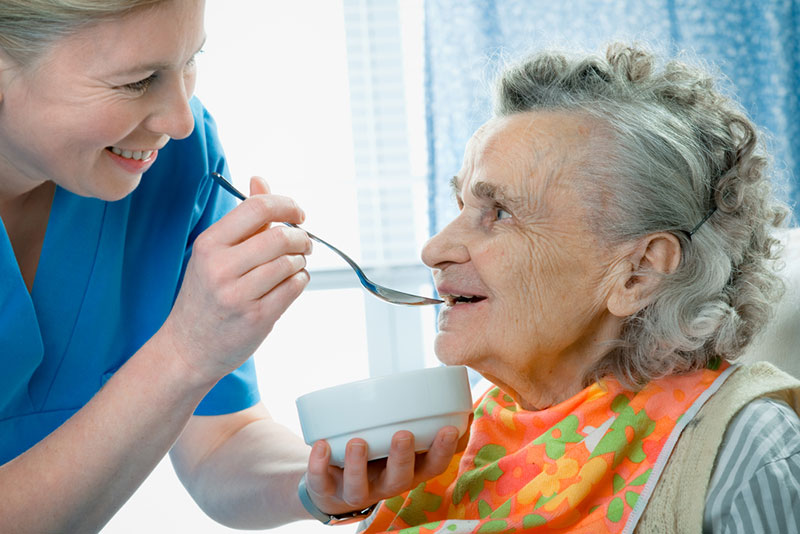 Elderly woman being fed by caretaker