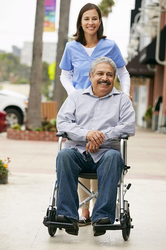 Carer Pushing Disabled Senior Man In Wheelchair