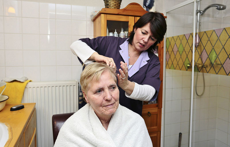 A caregiver helps an elderly woman with her hair